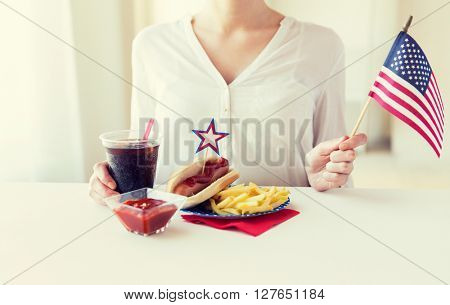 independence day, celebration, patriotism and holidays concept - close up of woman hands with hot dog and french fries holding american flag and cola drink on 4th july at home party