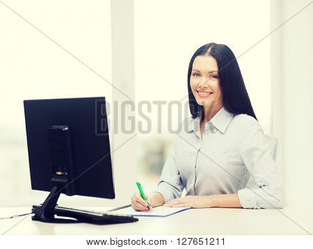 education, school, business and technology concept - smiling businesswoman or student studying