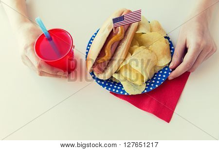 independence day, celebration, patriotism and holidays concept - close up of woman hands eating hot dog with american flag decoration, potato chips and juice in cup on 4th july at home party