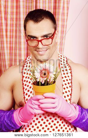 Smiling muscular man in an apron stands with a flower  in the pink kitchen. Love concept. Valentine's day. Women's day.