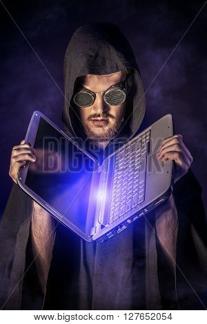 A hacker hiding his face behind glasses and a hood holds his laptop. Programmer.