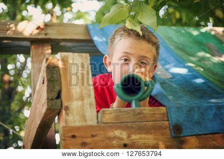 Boy looking through telescope in his fort