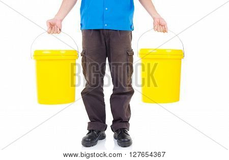 Production worker carrying two buckets of lubricant oils and greases isolated on white background.