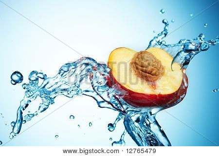 Peach in spray of water. Juicy peach with splash on background
