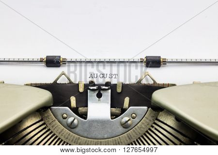 Close-up of word August on typewriter sheet