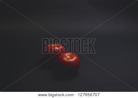 A red fresh tomatoes on a black table
