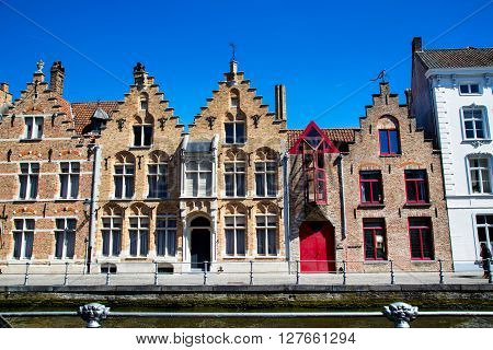 The row of colorful traditional houses in Brugge, Belguim against blue sky