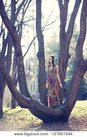 Hippie standing among the branches of a tree