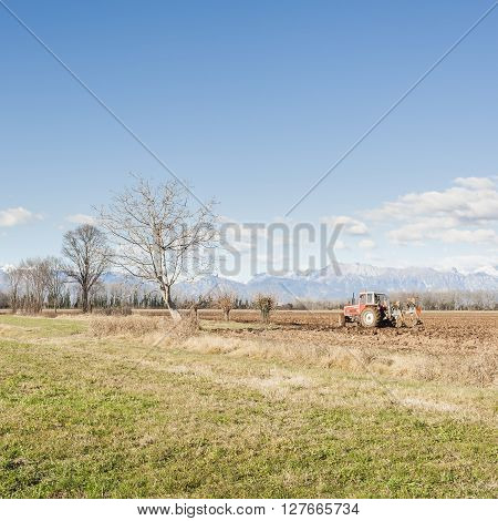 Agricultural landscape. With tractor plowing a field. The mountains in the background.