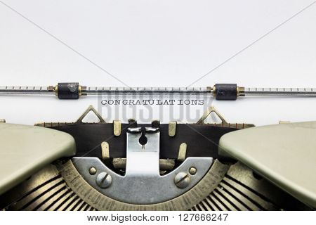 Close-up of congratulations word in capital letters on white paper in typewriter