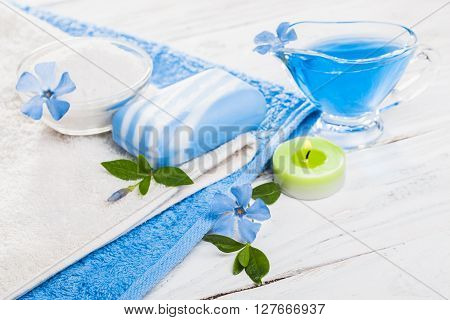 Spa still life of sea salt and essential oils and periwinkle flowers ** Note: Shallow depth of field