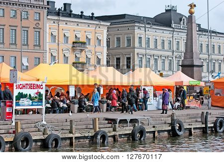HELSINKI, FINLAND - APRIL 23, 2016: People in open air cafe on The Market Square near Gulf of Finland in the center of Helsinki.  On the right side is The Tsarinas Stone Obelisk