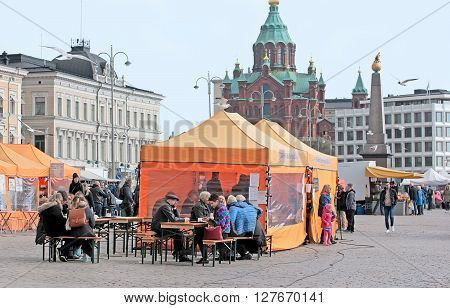 HELSINKI, FINLAND - APRIL 23, 2016: People in open air cafe on The Market Square near Gulf of Finland in the center of Helsinki. On the background is The Uspenski Cathedral