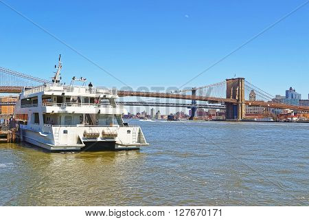 Ferry and and Brooklyn bridge across East River New York USA. Brooklyn Bridge is among the oldest bridges in the United States of America. Brooklyn Heights on the right. Tourists on the boat.