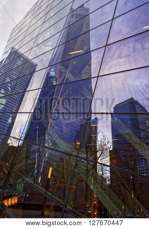 New York, USA - April 24, 2015: One World Trade Center skyscraper reflected in a glass building in Financial District Lower Manhattan New York City USA.