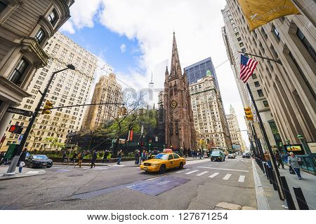 Trinity Church In Manhattan And Street With Tourists And Traffic