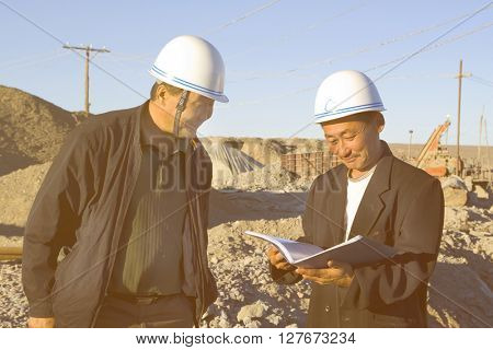 Construction Workers Reading The Note In The Construction Site Concept