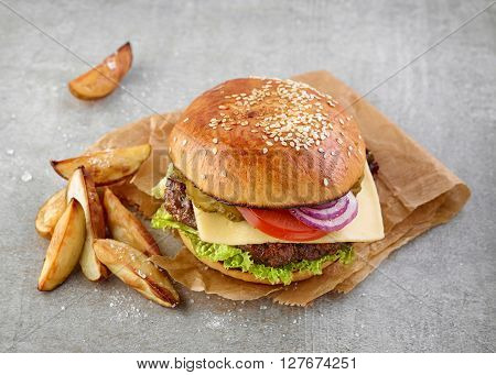 Classic cheeseburger and potato wedges on gray table