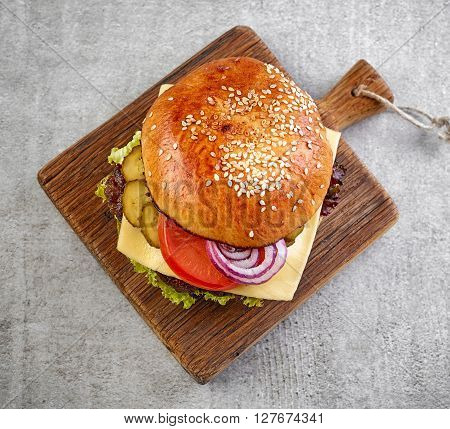 Classic cheeseburger on grey table, top view