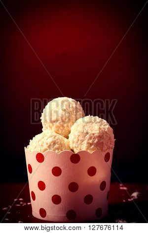 Coconut pralines in the cup on red background with blank space above