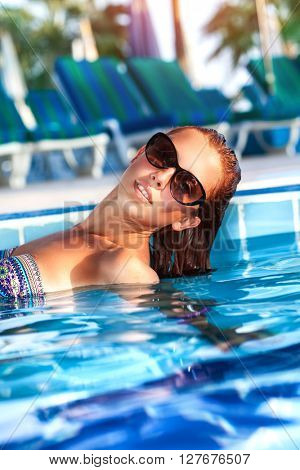 Fashion portrait of a beautiful woman in the swimming pool on the beach resort, enjoying cold refreshing water in hot summer day