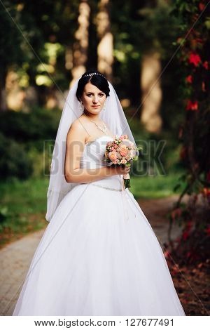 Portrait of beautiful young brunette bride in elegant dress with bouquet of pink flowers in the autumn park
