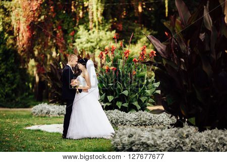 Beautiful bride and handsome groom at wedding day lovely hugging outdoors on nature with copy space. Bridal couple happy newlywed woman and man embracing in green park. Loving wedding couple outdoor.
