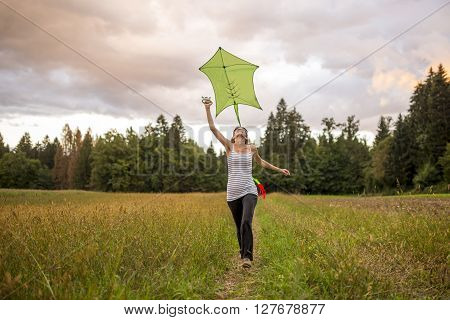 Young woman flying a green kite running through a beautiful autumn meadow with forest in background.