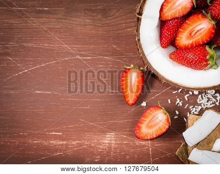 Half coconut with strawberries and wedges of coconut and shredded coconut on dark wooden background