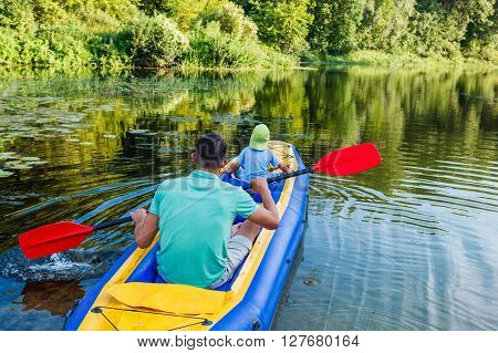 Active happy family. Back view of father with his son having fun together enjoying adventurous experience kayaking on the river on a sunny day during summer vacation