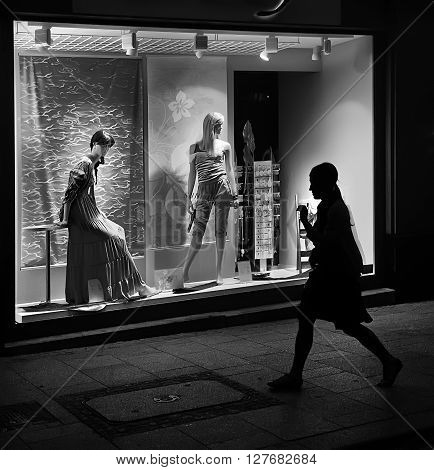 KRAKOW, POLAND - JUNE 6: Woman walking past the mannequins in illuminated shop window June 6, 2011 in Krakow, Poland. Krakow is a popular destination for shopping