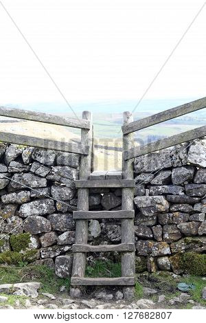 Wooden Stile going over a dry stone wall on the Pennine Way in Malham Cove Yorkshire UK