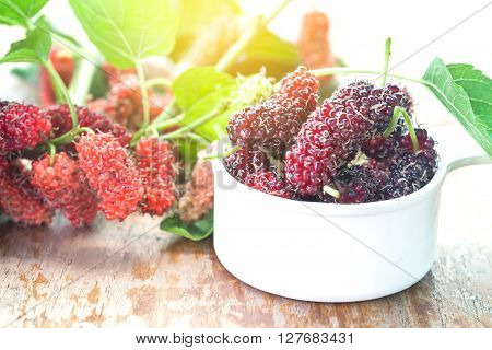 Mulberry in bowl on wooden background. Selective focus
