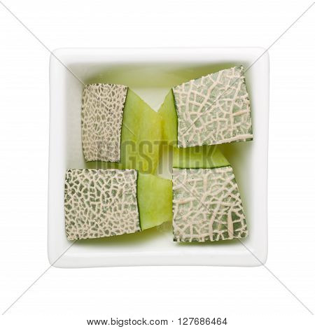 Pieces of cantaloupe in a square bowl isolated on white background