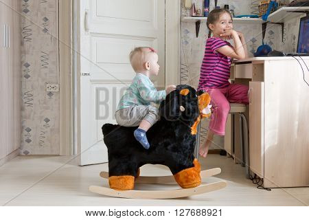 Girls playing at home as usual. Five year old girl watching cartoons on the notebook, and her kid sister swinging on a rocking horse