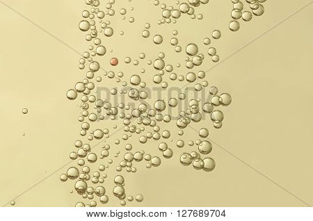 Golden champagne carbonated bubbles over a blurred background