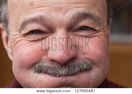 Elderly man barely holding back laughter, puffing out his cheeks