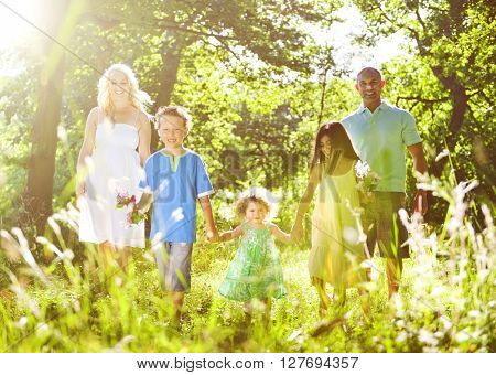 Family holding hands walking together through the woods.