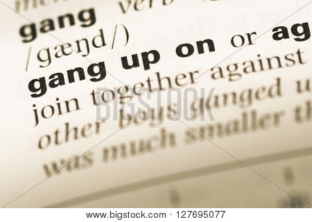 Close Up Of Old English Dictionary Page With Word Gang Up On.