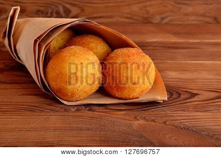 Arancini balls. Fried rice balls in paper on brown wooden background. Snack