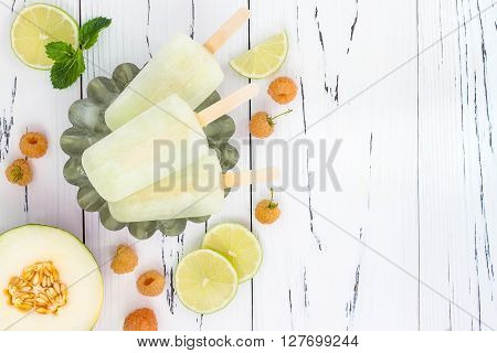 Refreshing mexican style ice pops - raspberry lime honeydew margarita paletas - popsicles. Top view overhead. Cinco de Mayo recipe copy space
