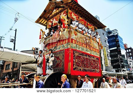 KYOTO JAPAN-  July 17th 2011 : A highly decorated float along with its accompanying men in traditional Japanese clothes is being dragged in a parade during the Gion Matsuri of July 17th 2011 in Kyoto Japan.