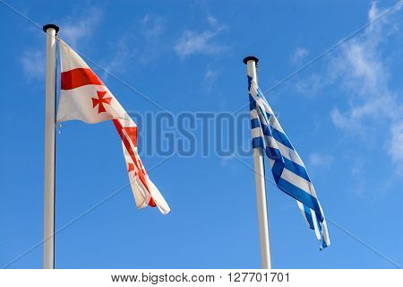 flags of Greece and Georgia on the background of the sky