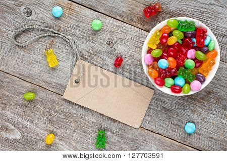 Blank tag and bowl with mixed candies on wooden background