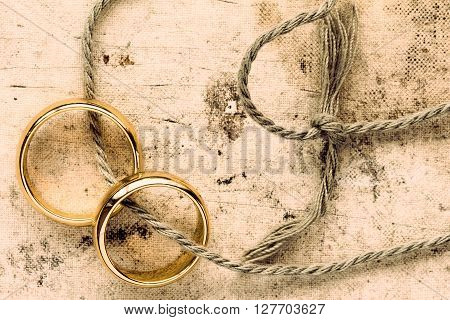 Two gold wedding rings tied with string