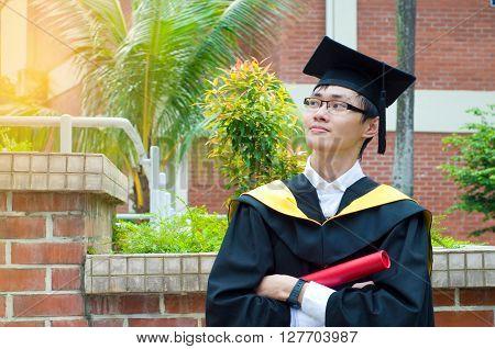 Confident asian university graduate in the college
