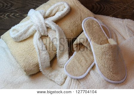 Terry cloth towel and bath slippers lying on a dressing gown.