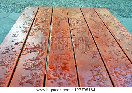 water drop on a wooden table outside after rainfall