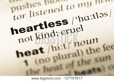 Close Up Of Old English Dictionary Page With Word Heartless.