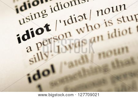 Close Up Of Old English Dictionary Page With Word Idiot.